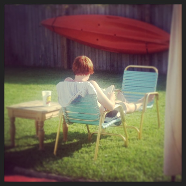 A boy.  Reading and relaxing after an afternoon of lawn mowing.
