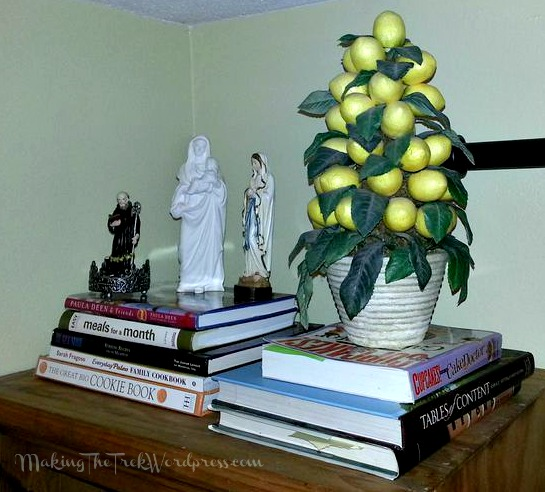 Top o' the shelf with miscellaneous books and our Saint Benedict and Mary statues.